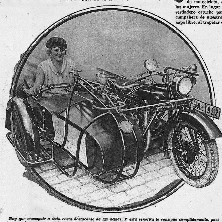 Se muestra una mujer de la época montada en un sidecar de una motocicleta, con las manos en el manillas.
