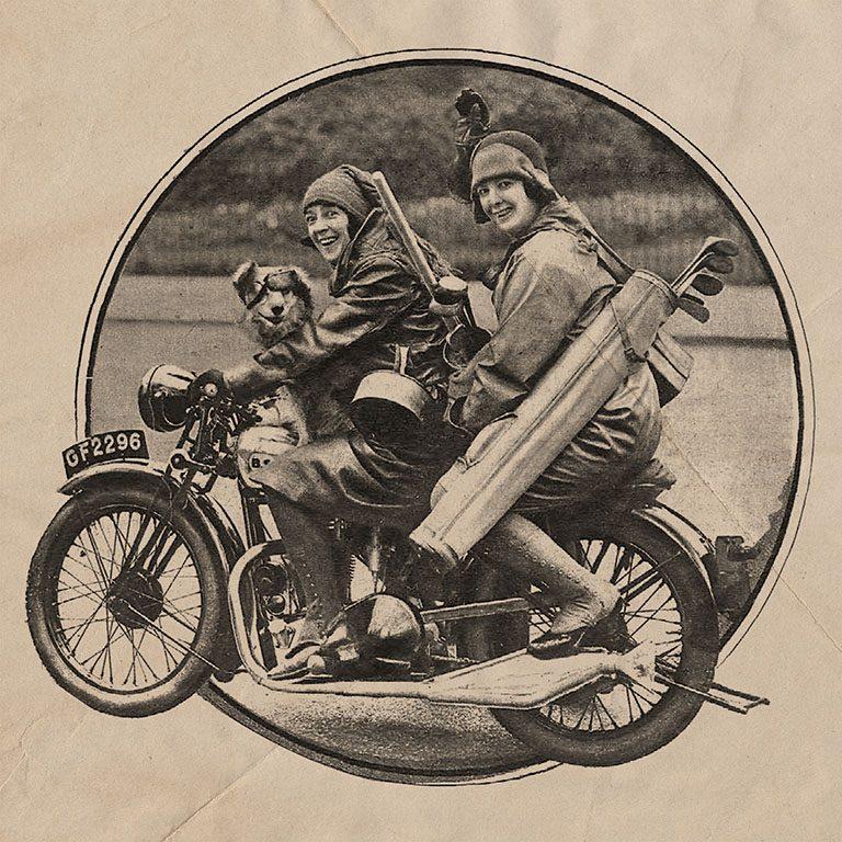 Dos mujeres montadas en una moto, con un perro. Ambas llevan gorros de la época y miran a la cámara riendo. Llevan cacerolas, cosas para un picnic, palos para jugar al polo...